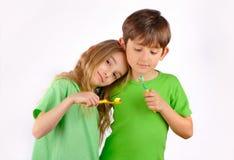 Vård- - pojken och flickan borstar deras tänder Arkivbilder