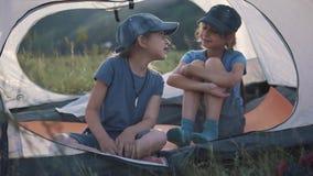 Barn pratar glatt, medan sitta i ett tält utomhus handelsresande för två små flickor lager videofilmer