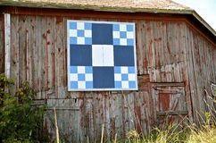 Barn quilt on old weathered building. Stock Images