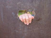 Barn räcker med små fingrar till och med hålet i träklättringväggstege på ungelekplats Arkivfoton