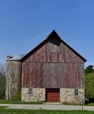 Barn With A Red Door. This is a Picture of a large barn featuring a limerock foundation, a silo, and a red door located in a Cass County, North Dakota.  This Stock Image
