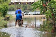 Barn rider en cykel till och med floden Arkivbilder