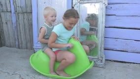 Barn rider på den gröna plast- hästen som vaggar på bakgrund av speglar i borggård av det lantliga huset härliga ungar arkivfilmer