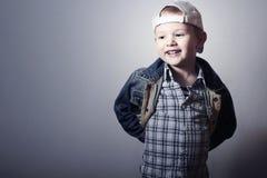 Barn. Roliga Little Boy i jeans. Lastbilsförarelock. glädje. Trendig unge. plädskjorta. Grov bomullstvillkläder Arkivfoton