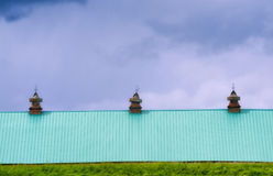 Barn roof against cloudy skies. A hill of grass hides all but the roof of a barn it& x27;s teal colored metal roof contrast nicely against cloudy skies in rural Royalty Free Stock Image