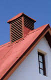 Barn roof detail. Detail of a red corrugated iron barn roof against a blue sky Royalty Free Stock Image