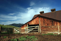 Barn Rural. Rural of old weathered log barn and wood fence on ranch in the mountains royalty free stock photo