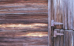 Barn with Rusty Hinges. The side of a barn showing part of two barn doors with very weathered and rusty hinges Royalty Free Stock Photography