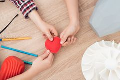 Barn rymmer en röd hjärta utskrivaven på en skrivare 3d Royaltyfria Foton