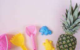 Barn sätter på land leksaker och ananas på pastellfärgad rosa bakgrund sommar f?r sn?ckskal f?r sand f?r bakgrundsbegreppsram Lek royaltyfri foto