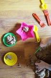 Barn` s räcker att spela med kinetisk sand och färgrika plast- leksaker royaltyfria bilder