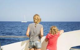 Barn ser havet från däcket av ett fartyg Arkivbild
