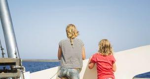 Barn ser havet från däcket av ett fartyg Arkivfoto