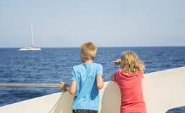 Barn ser havet från fartygdäcket Arkivbilder