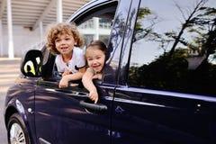 Barn ser ut från ett bilfönster Royaltyfri Foto