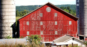 Barn and silos. Family farm has barn with weathered red paint and two silos. Barn built in 1872 stock photo