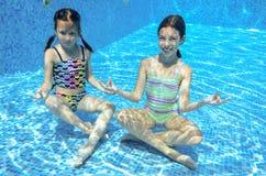 Barn simmar i den undervattens- pölen, lyckliga aktiva flickor har gyckel under vatten Royaltyfri Foto