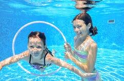 Barn simmar i den undervattens- pölen, lyckliga aktiva flickor har gyckel under vatten Royaltyfria Bilder