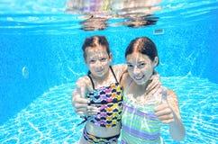 Barn simmar i den undervattens- pölen, lyckliga aktiva flickor har gyckel under vatten Royaltyfri Bild