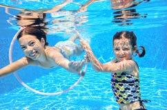 Barn simmar i den undervattens- pölen, lyckliga aktiva flickor har gyckel under vatten, ungesport Royaltyfri Bild
