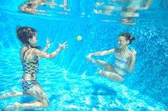 Barn simmar i den undervattens- pölen, lyckliga aktiva flickor har gyckel under vatten, ungesport Royaltyfria Bilder