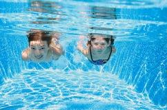 Barn simmar i den undervattens- pölen, lyckliga aktiva flickor har gyckel i vatten, ungekondition och sport på familjsemester Arkivbilder