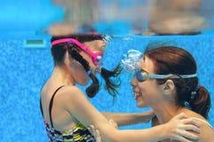 Barn simmar i den undervattens- pölen, lyckliga aktiva flickor i skyddsglasögon har gyckel under vatten, ungesport Royaltyfri Bild