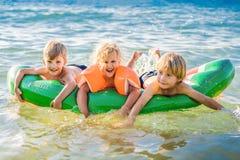 Barn simmar i havet p? en uppbl?sbar madrass och har roligt royaltyfria bilder