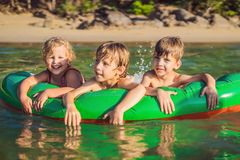 Barn simmar i havet p? en uppbl?sbar madrass och har roligt fotografering för bildbyråer