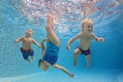 Barn simmar och dyker undervattens- med gyckel i simbassäng Royaltyfria Foton