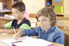 Barn sitter i klassrumet Arkivbilder