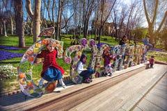 Barn sitter på det skulpturala blommasymbolet av Gulhane parkerar Arkivfoto
