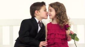Barn sitter på en gunga och ett samtal, i handen för flicka` s en ros Vit bakgrund långsam rörelse close upp lager videofilmer