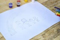 Barn skissar med blyerts Familj och regnbåge royaltyfri fotografi