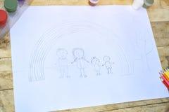 Barn skissar med blyerts Familj och regnbåge royaltyfria bilder