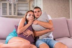 Barn skrämde par som håller ögonen på den läskiga filmen på TV Royaltyfri Foto