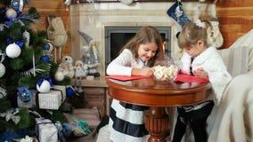 Barn skrivar brevet för Santa Claus, systrar som äter sötsaker, flickor sitter nära spisen, barn nära julgranen stock video