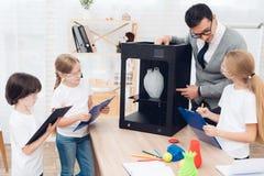 Barn skrivar ut olika objekt på en skrivare 3d med en lärare Royaltyfri Bild