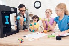 Barn skrivar ut olika objekt på en skrivare 3d med en lärare Arkivfoto