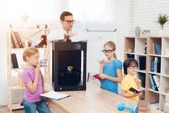 Barn skrivar ut olika objekt på en skrivare 3d med en lärare Royaltyfri Fotografi