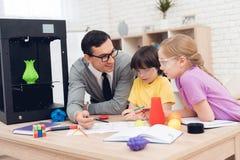 Barn skrivar ut olika objekt på en skrivare 3d med en lärare Royaltyfria Bilder