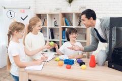 Barn skrivar ut olika objekt på en skrivare 3d med en lärare Arkivbild