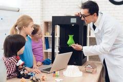 Barn skrivar ut olika objekt på en skrivare 3d med en lärare Arkivfoton