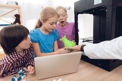 Barn skrivar ut olika objekt på en skrivare 3d med en lärare Royaltyfri Foto