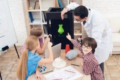 Barn skrivar ut olika objekt på en skrivare 3d med en lärare Fotografering för Bildbyråer