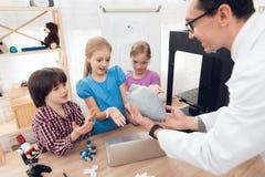 Barn skrivar ut olika objekt på en skrivare 3d med en lärare Royaltyfria Foton