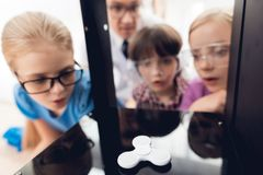Barn skrivar ut olika objekt på en skrivare 3d med en lärare Arkivbilder