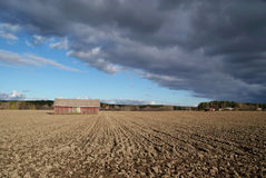 Barn, Sky and Ploughed Field Landscape. An autumnal landscape with a red barn and a dark cloud casting a shadow over the ploughed field. Photographed in Salo Royalty Free Stock Photo