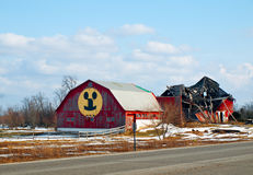 Optimism. Barn with smiley face next to collasped barn structure Stock Image