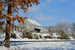 Barn in snow behind train tracks Royalty Free Stock Photography
